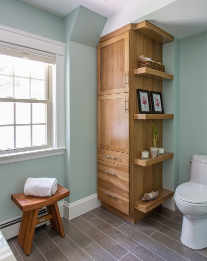 This tall cabinet by Showplace cabinetry allows ample linen storage and unique floating shelves attached to the side.